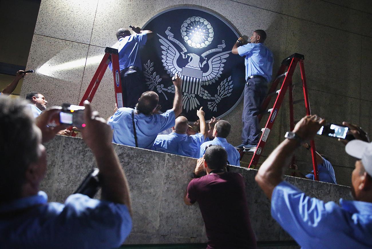 Гавана, Куба. Сотрудники посольства США вешают герб Соединенных Штатов на фасаде посольства за несколько часов до торжественного поднятия флага. Фото Chip Somodevilla/Getty Images