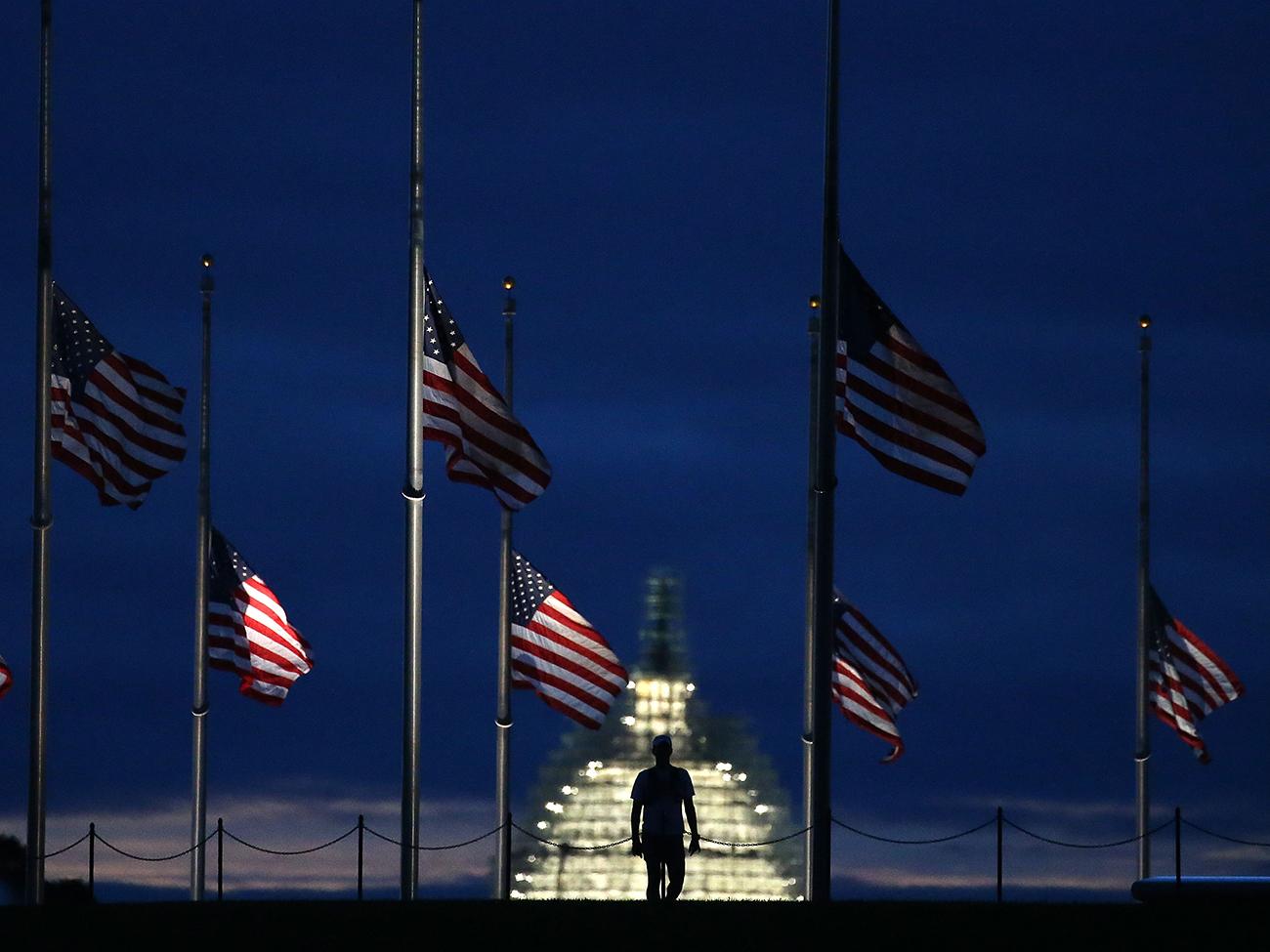Вашингтон, округ Колумбия. Человек проходит мимо американских флагов, приспущенных в память о терактах во Всемирном торговом центре и Пентагоне. 11 сентября исполнилось 14 лет со дня трагедии. Фото Mark Wilson/Getty Images