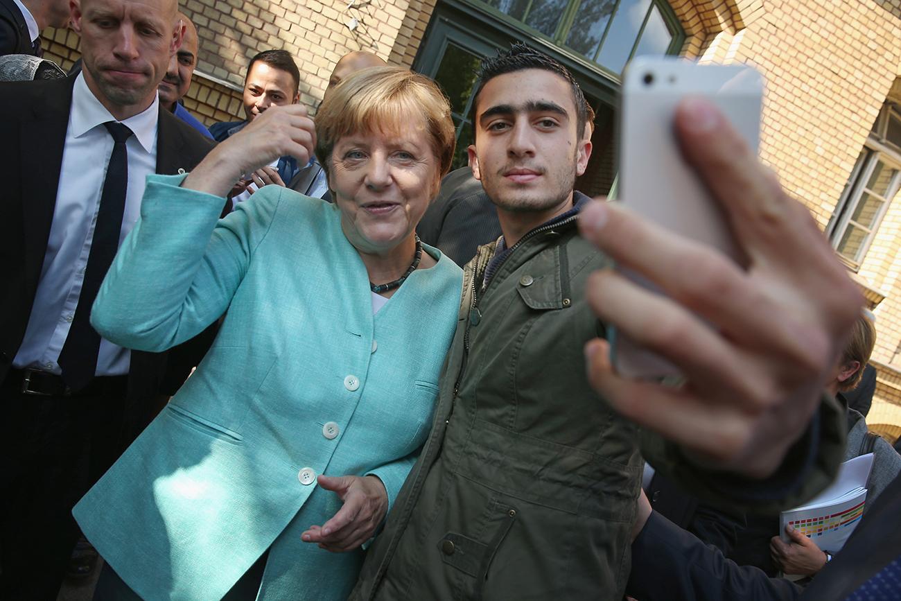 Берлин, Германия. Канцлер Ангела Меркель позирует для селфи мигранта из Сирии в приюте для мигрантов AWO Refugium Askanierring. Фото Sean Gallup/Getty Images