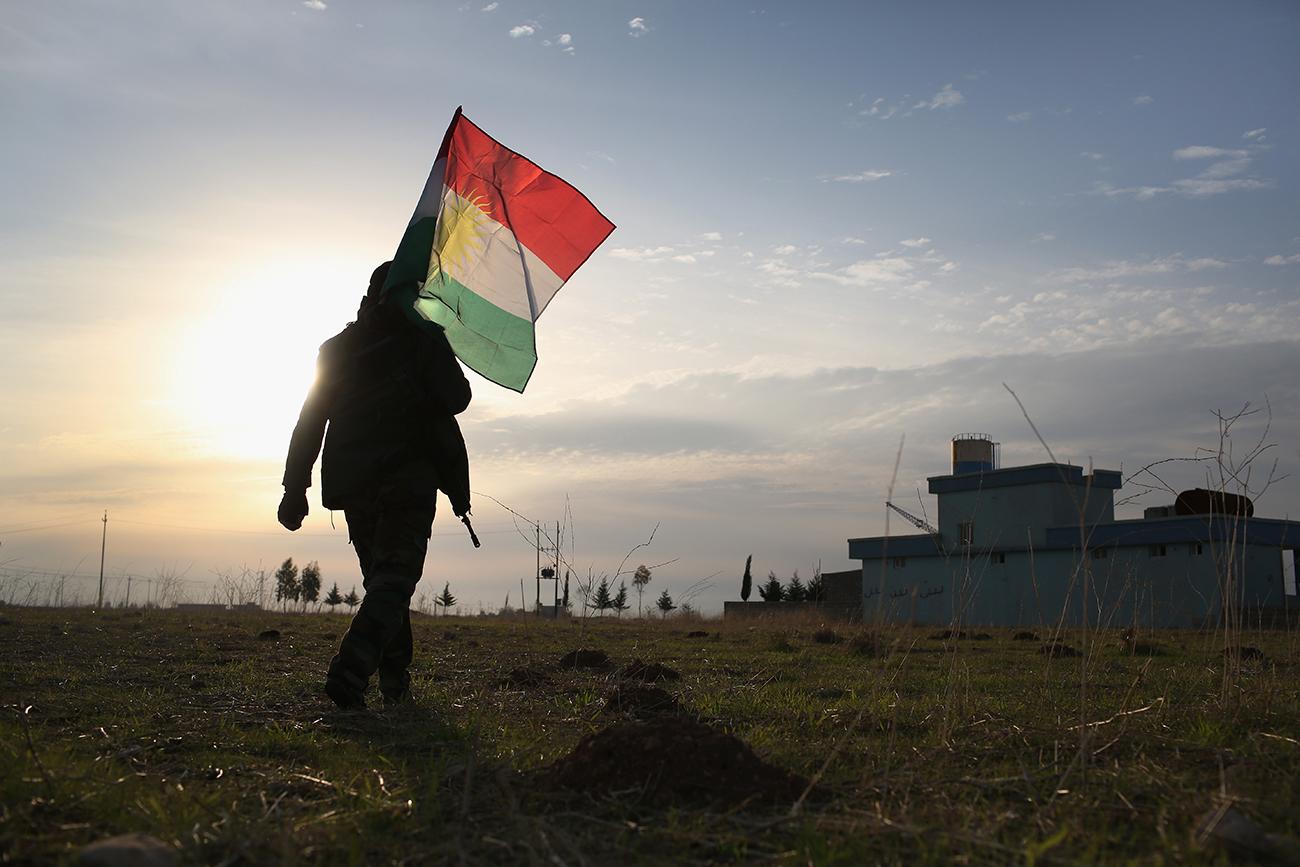 Синджар, Ирак. Солдат пешмерга идёт воодружать курдский флаг возле линии фронта с ИГИЛ.