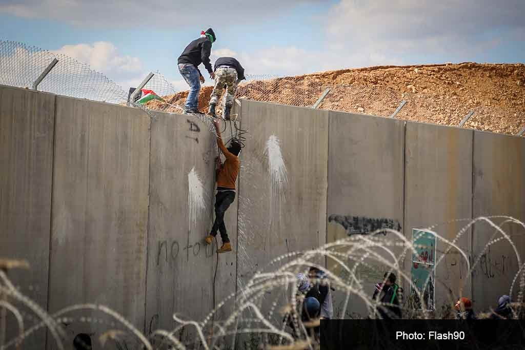Палестинцы перелезают через разделительный забор около Рамаллы